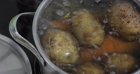 cooktop : Hot boiling pan with vegetables potatoes and carrots. Cooking in a pan on the home kitchen Stock Footage