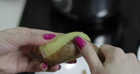 starch : Female housewife hands peeling potatoes in the kitchen with a knife Stock Footage