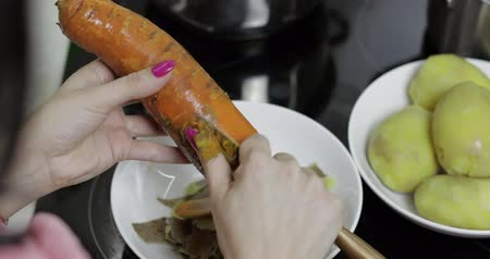 крахмал : Female housewife hands peeling carrot in the kitchen with a knife Стоковые видеозаписи