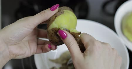крахмал : Female housewife hands peeling potatoes in the kitchen with a knife Стоковые видеозаписи