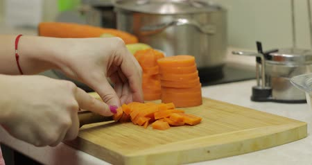 крахмал : Female housewife hands slicing carrots into pieces on the wooden cutting board in the kitchen