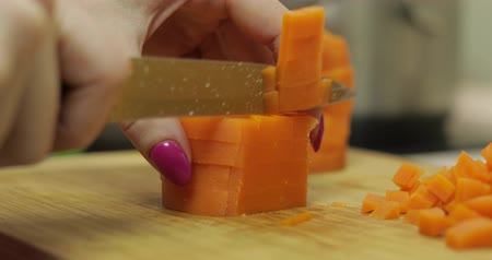 チョッピング : Female housewife hands slicing carrots into pieces on the wooden cutting board in the kitchen
