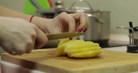 крахмал : Female housewife hands slicing potatoes into pieces on the wooden cutting board in the kitchen
