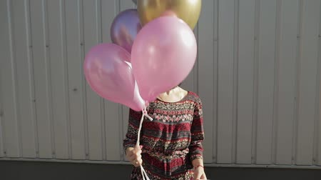 幼稚な : Pretty girl in dress holding multicolored balloons with helium outdoors in daylight. Woman going to birthday party. Slow motion
