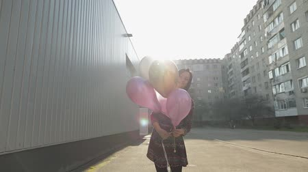 dětinský : Pretty girl in dress holding multicolored balloons with helium outdoors in daylight. Woman going to birthday party. Slow motion