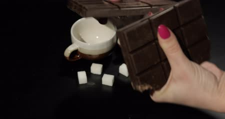 yermantarı : Woman breaks black chocolate bar. Close-up shot of woman fingers which breaking the chocolate