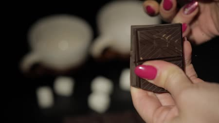 yermantarı : Woman breaks black chocolate bar. Close-up shot of woman fingers which breaking the chocolate. Slow motion