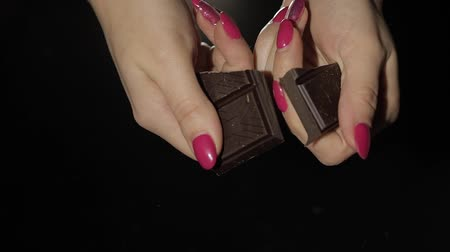 mentiras : Woman breaks black chocolate bar. Close-up shot of woman fingers which breaking the chocolate. Slow motion