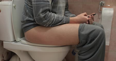 toilet paper : Man Sitting On Toilet Use Cell Smart Phone. Young Guy Chatting Online In Restroom Stock Footage