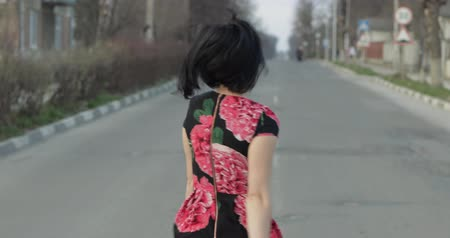 go away : Attractive young woman in a dress with flowers turns to camera and smiles seductively, continues walking away from the camera. Shows fingers to follow her. Walking on the highway. Close-up shot Stock Footage