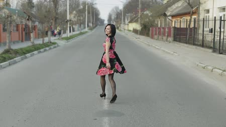 caminhada : Attractive young woman in a dress with flowers turns to camera and smiles seductively, continues walking away from the camera. Cute girl walking on the highway. Slow motion Vídeos