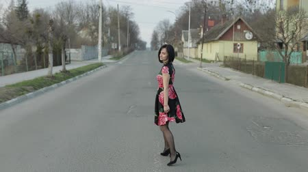 go away : Attractive young woman in a dress with flowers turns to camera and smiles seductively, continues walking away from the camera. Cute girl walking on the highway. Slow motion Stock Footage