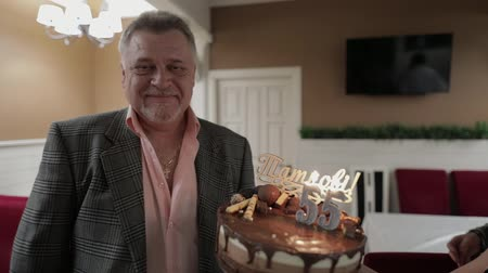 diabetis : Happy respectable old man holding cake. Celebrating birthday anniversary at restaurant. Businessman with gray hair. Two candles at cake. slow motion Archivo de Video