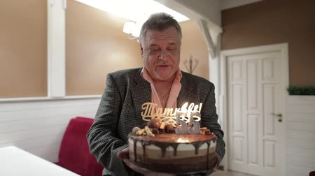 grandfather : Happy respectable old man holding cake. Celebrating birthday anniversary at restaurant. Businessman with gray hair. Two candles at cake. slow motion Stock Footage
