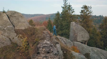 keresztül : Young man goes down the hill of a high mountain in the forest park. Businessman is in a good costume. Holds his jacket across the shoulder. Bridegroom. Groom. Colorful autumn. Aerial view