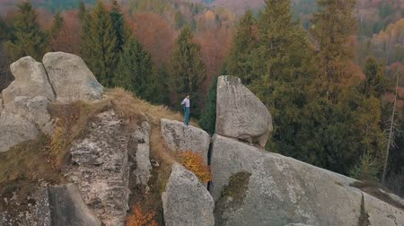 жених : Young man on the hill of a high mountain in the forest park. Businessman is in a good costume. Dress up his blue jacket. Bridegroom. Groom. Colorful autumn. Aerial view
