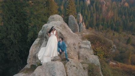 sklon : Wedding couple stand on a high slope of the mountain hills near forest. Lovely groom and bride. Happy family. Man and woman in love. Wedding day. Aerial view. Shot from drone