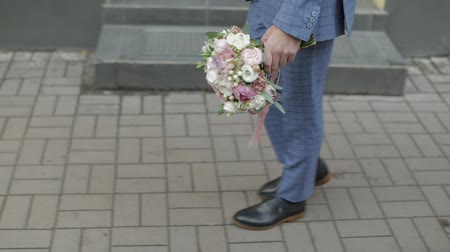 жених : Groom dressed in blue suit, and blue shoes walking to his bride holding wedding bouquet of white and pink flowers in hand. Anonymous man. Slow motion video footage
