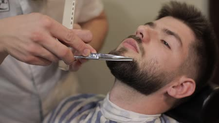 аксессуары : Client with black beard during beard shaving in barber shop. Groom, care, masculine. Vintage styling tools. Luxurious hairdressing concept. Slow motion Стоковые видеозаписи