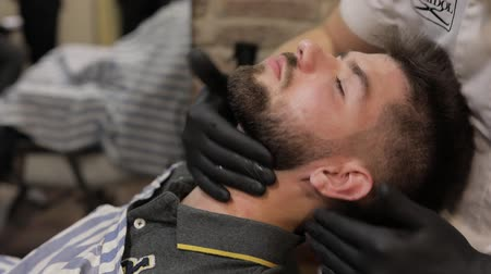 barber hair cut : Client with black beard during beard shaving in barber shop. Groom, care, masculine. Vintage styling tools. Luxurious hairdressing concept. Slow motion Stock Footage