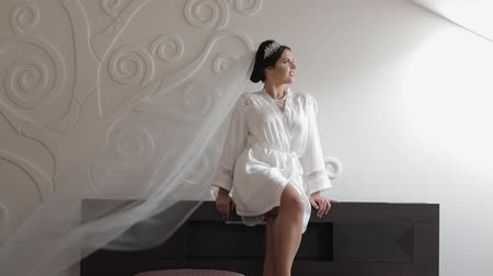 závoj : Beautiful and lovely bride in night gown and veil. Pretty and well-groomed woman in bedroom. Wedding morning. Slow motion