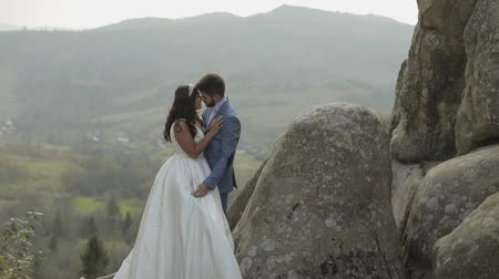 невеста : Groom with bride on a mountain hills in the forest. Wedding couple. Happy family. Man and woman in love. Lovely groom and bride. Wedding day. Slow motion