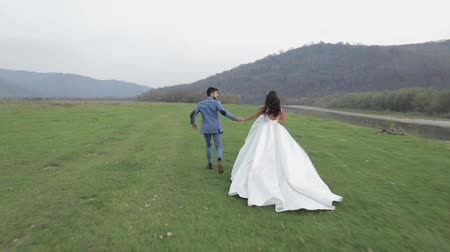 традиция : Wedding couple running near mountain river. Lovely groom and bride. Happy family. Man and woman in love. Wedding day.