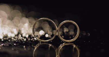 elszigetelt fekete : Wedding rings on dark water surface shining with light. Close up macro.