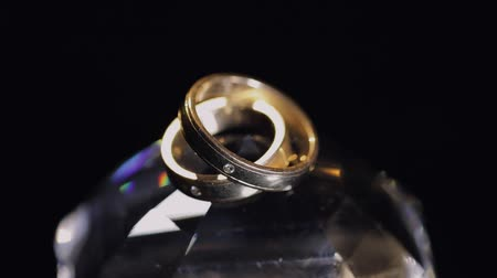pedra preciosa : Wedding rings lying on crystal shining with light close up macro. Black background. Slow motion