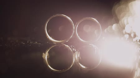 kıymetli : Wedding rings on dark water surface shining with light. Close up macro.