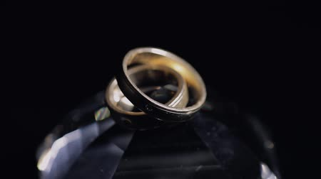 elszigetelt fekete : Wedding rings lying on crystal shining with light close up macro. Black background. Slow motion