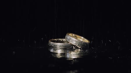 background gold : Wedding rings on dark water surface shining with light. Close up macro.