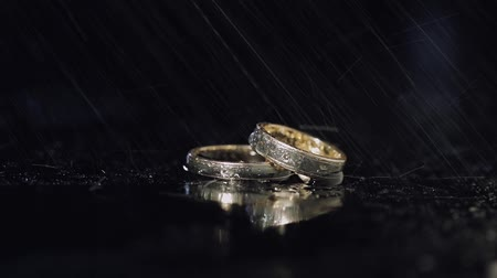 precioso : Wedding rings on dark water surface shining with light. Close up macro.
