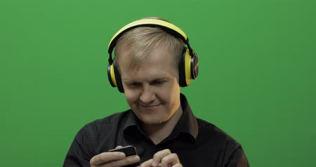 alkalmazottak : Guy listens to energetic music in wireless yellow headphones and dances. Portrait of attractive man using smart phone for listening the music in headphone while sitting near green screen. Chroma key