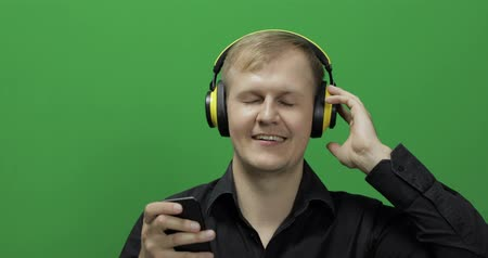 chime : Guy listens to energetic music in wireless yellow headphones and dances. Portrait of attractive man using smart phone for listening the music in headphone while sitting near green screen. Chroma key