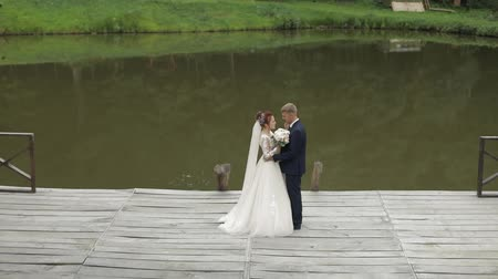 невеста : Groom with bride near lake in the park. Wedding couple. Happy family. Man and woman in love. Lovely groom and bride. Slow motion Стоковые видеозаписи