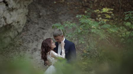 závoj : Groom with bride stand in the forest park near mountain hills. Wedding couple. Happy family. Man and woman in love. Lovely groom and bride. Slow motion