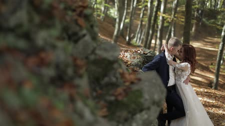 závoj : Groom with bride in the forest park near mountain hills. Wedding couple. Happy family. Man and woman in love. Lovely groom and bride. Making a kiss. Slow motion