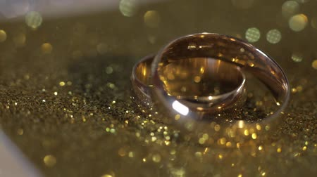 аксессуары : Wedding gold rings lying on shiny glossy surface. Shining with light. Close-up, macro shot