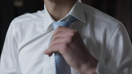 cravatta : Handsome groom fixes his white shirt with blue bow tie. Wedding morning. Businessman. Close-up shot. Slow motion
