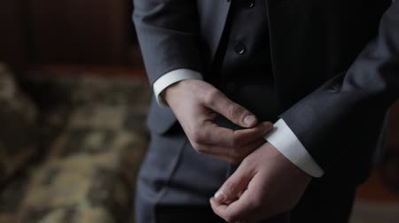 manşet : Handsome groom fixes his cuffs on a jacket. White shirt. Wedding morning. Businessman. Close-up shot. Slow motion