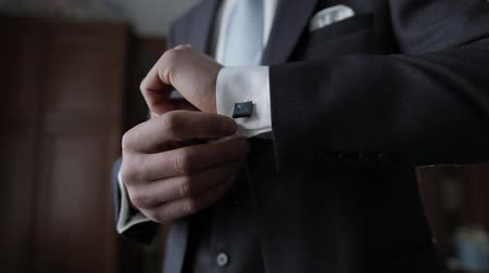 manşet : Handsome groom fixes his cuffs on a jacket. White shirt with cufflinks. Wedding morning. Businessman. Close-up shot. Slow motion