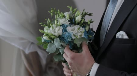 perfumy : Groom with wedding bouquet in his hands at home near window. White shirt, blue tie and jacket. Wedding day. Handsome man. Businessman. Close-up shot. Slow motion Wideo