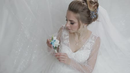 sıkmak : Bride in wedding dress with small bouquet with blue and white flowers in her hands. Pretty and well-groomed woman. Wedding day. Slow motion