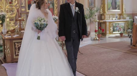 фехтование : Elegant bride and groom walking together in an old church. Wedding couple. Happy family. Slow motion