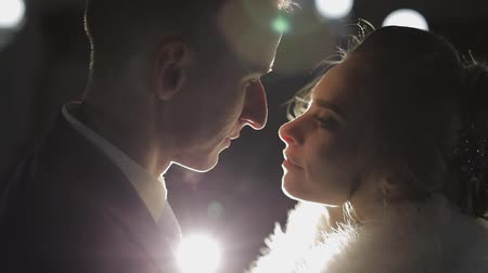 крытый : Groom with bride making a kiss in cold evening on a bridge covered with many lanterns. Autumn. Wedding couple. Happy family. Man and woman in love. Lovely groom and bride. Slow motion Стоковые видеозаписи