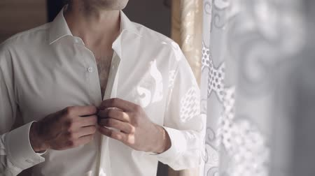trousers : Handsome groom fixes his shirt. Wedding morning. Slow motion.