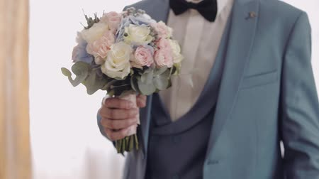 smokin : Handsome groom with beautiful wedding bouquet. Light background. Slow motion.