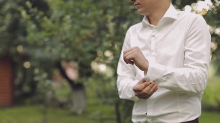 cravatta : Handsome groom fixes his shirt. Wedding morning. Slow motion.