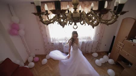 невеста : Beautiful and lovely bride in wedding dress dancing near window. Wedding morning. Pretty and well-groomed woman. Slow motion Стоковые видеозаписи